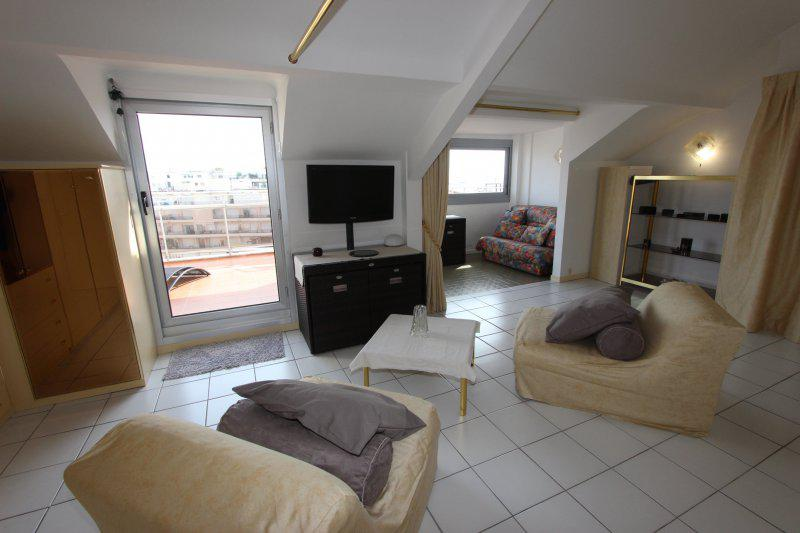 2 sofas with golden covers, a flat screen tv and a door to the terrace in the living room of a Cannes studio apartment