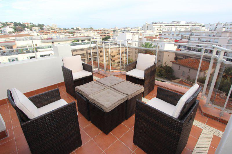 Brown chairs and table on the terrace of a Cannes rental accommodation with city views