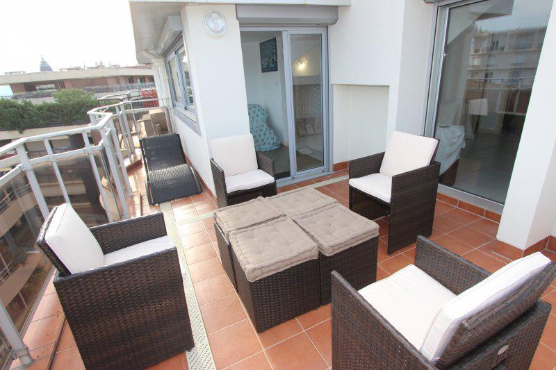 Terrace seating with table and a lounge chair in a Cannes group rental apartment