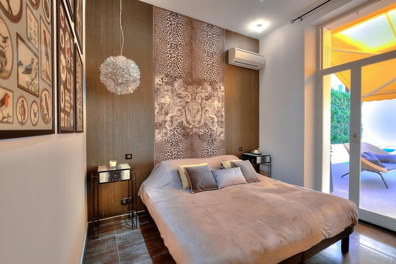 Double bed with wall paintings, wooden wall, air conditioner and door to the terrace in a Cannes