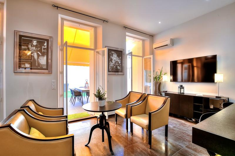 Yellow chairs with a round centre table, flat screen tv, wall paintings and view of outdoor terrace in Cannes