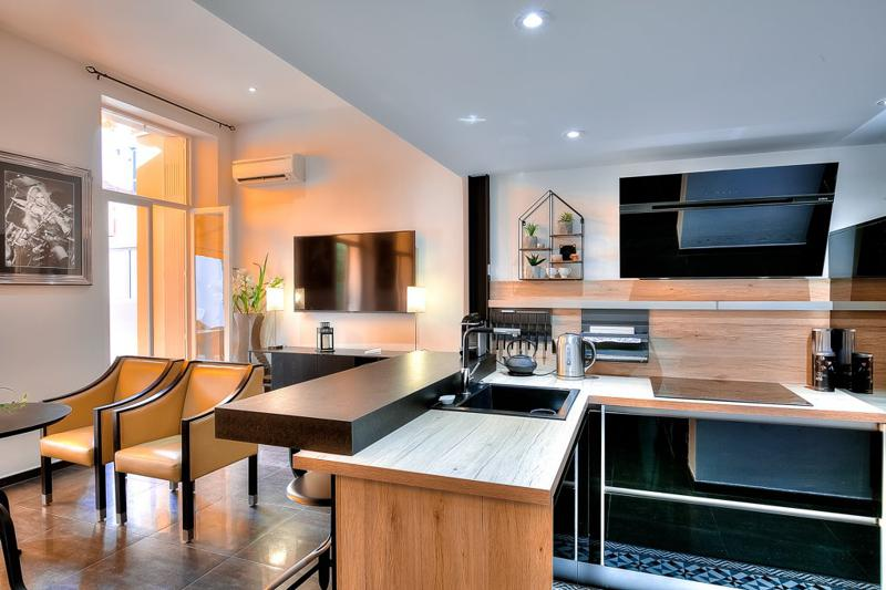 Open kitchen with coffee machine, induction stove and a living room with yellow chairs in a studio apartment in Cannes