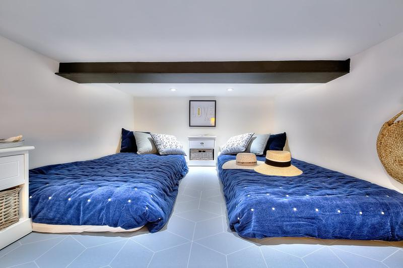 2 single beds with blue blankets and cushions in a Cannes rental studio apartment