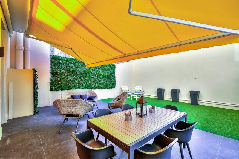 Cannes group apartment backyard with dining and relaxing area, a vertical wall garden and artificial turf