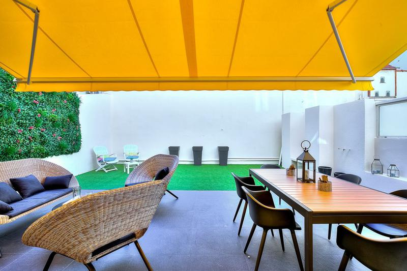 Dining table and couches in the outdoor terrace with a vertical and an artificial terrace gardens in Cannes group apartment