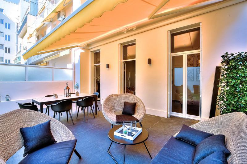 Couches and conference table for meetings in the outdoor seating area of a Cannes group accommodation