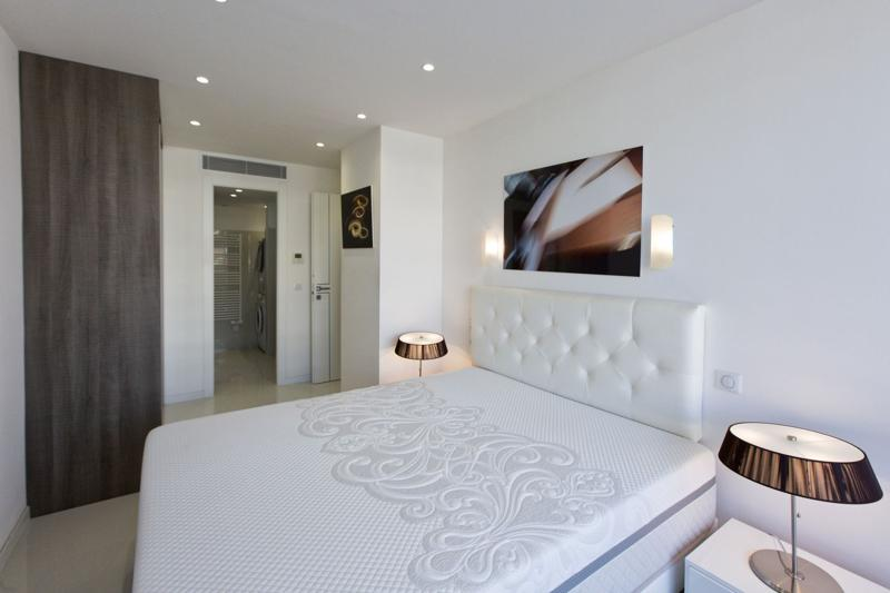 White walls and headboard in a double bedroom with an attached bathroom