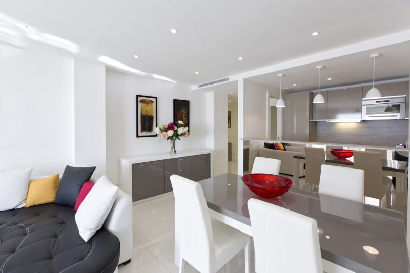 Modern living room with open kitchen and dining table with white chairs in a Cannes group accommodation for events