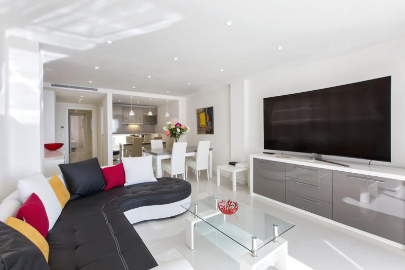 Black leather couches facing the tv, an open kitchen and meeting space in Cannes event accommodation for groups