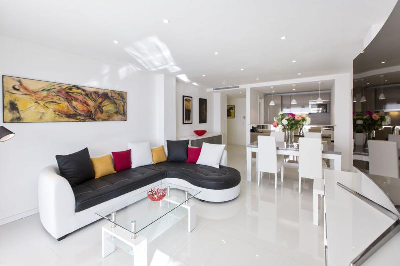 Marble floor in the living room with white walls, couch set, dining table and kitchen in a 2 bedroom Cannes rental apartment