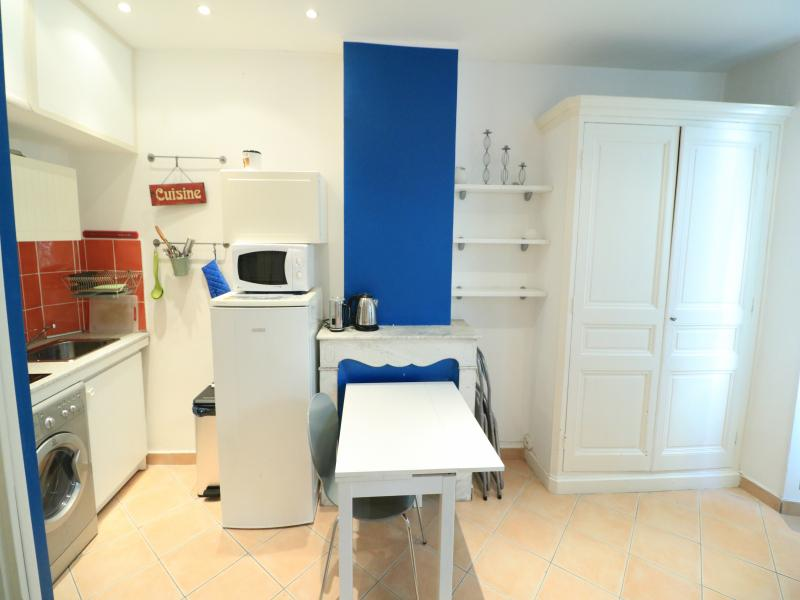 A white wardrobe and an open kitchen separated by a desk and a table in a Cannes studio apartment
