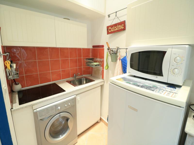 White walls and red tiles in a kitchen with washing machine, fridge, induction stove and a microwave