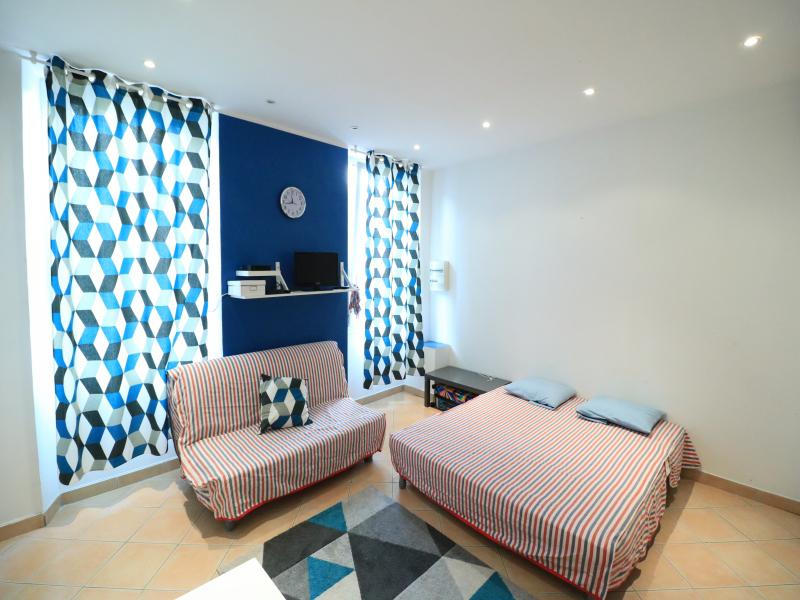 Double bed and couch with matching stripe covers in a Cannes rental studio apartment near the beach