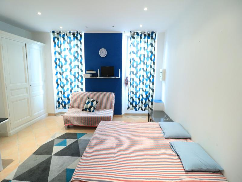 White wardrobe and window with curtains in a Cannes studio accommodation for rent near Palais des Festivals