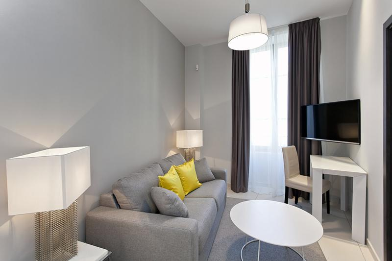 Living room with grey couch, round centre table and a flat screen tv in a Cannes 1 bedroom rental apartment
