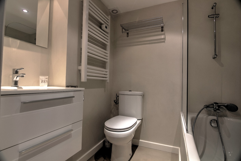Cream interiors in the bathroom with glass door shower, sink, mirror and toilet
