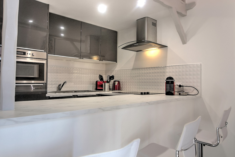 Open kitchen with coffee maker, toaster, microwave, induction stove and oven