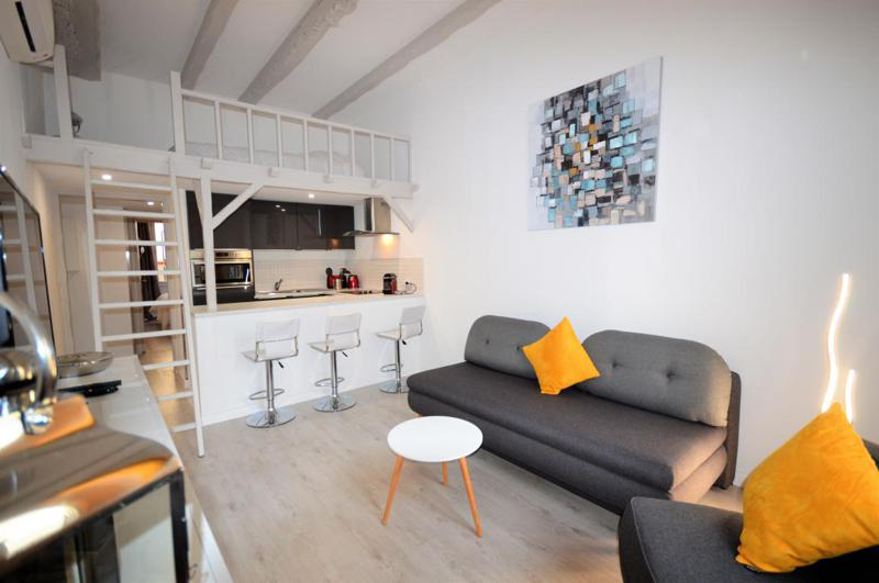 Mezzanine living room with a sofa bed, open kitchen and bar stools in a Cannes rental accommodation near Palais des Festival