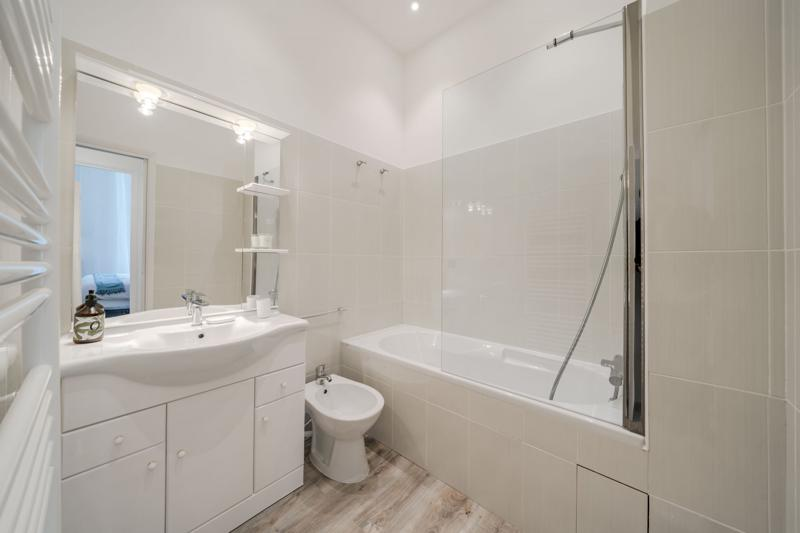 Cream tiles and white walls in a bathroom with bathtub in a Cannes group apartment