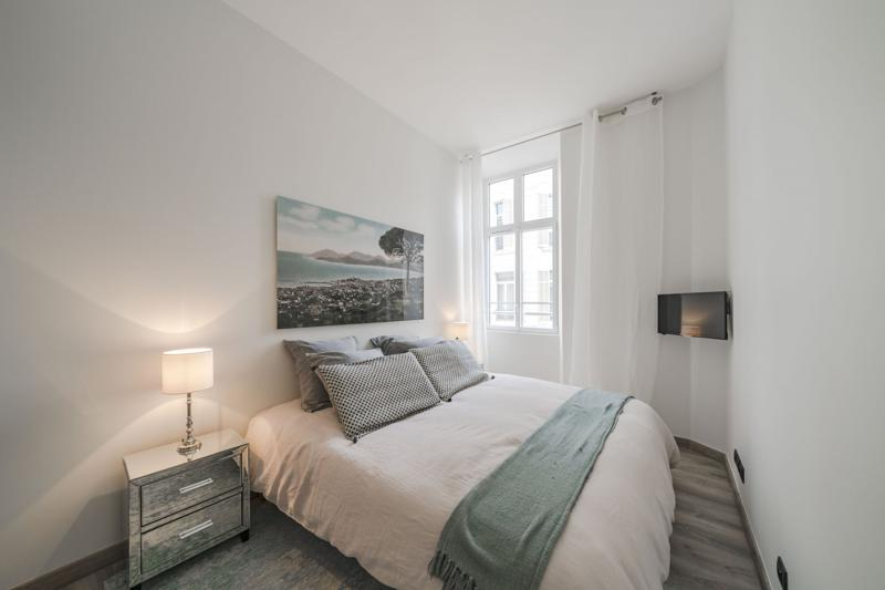 Double bedroom with a table lamp, natural light from the window and  tv in a Cannes apartment for rent