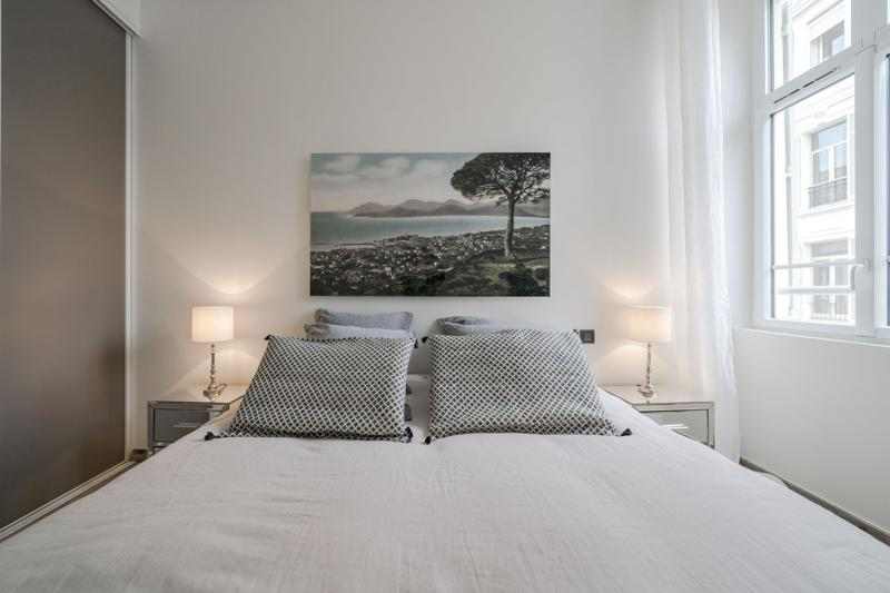Double bed with dotted cushions, 2 side tables and lamps,  painting on the wall behind and a window with views of Cannes