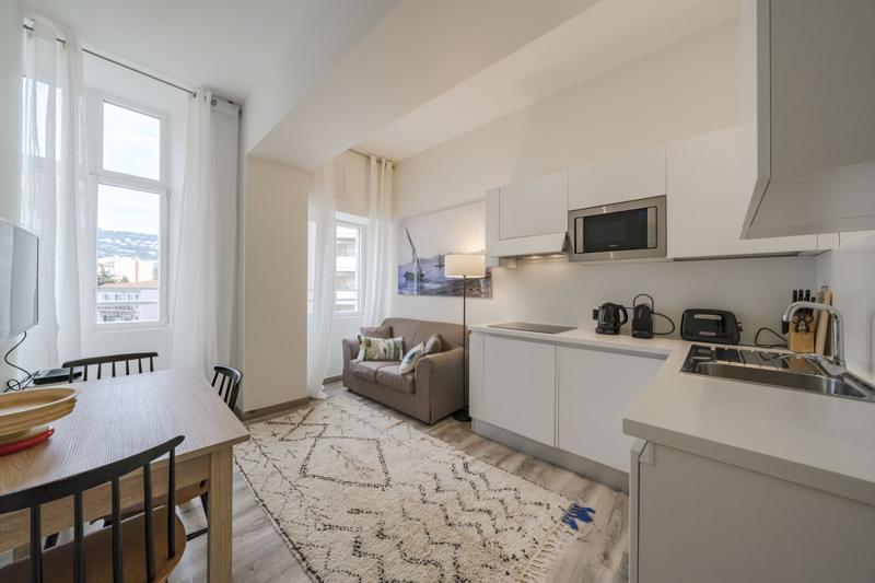 Living room with cream rug and open kitchen in a rental apartment with views of Cannes from the window