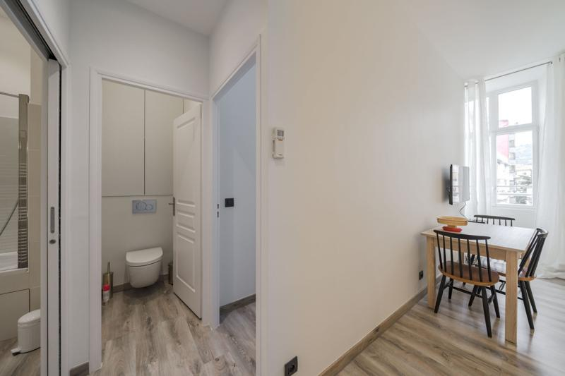 Open white bathroom door next to a wooden floored living room in a Cannes rental apartment