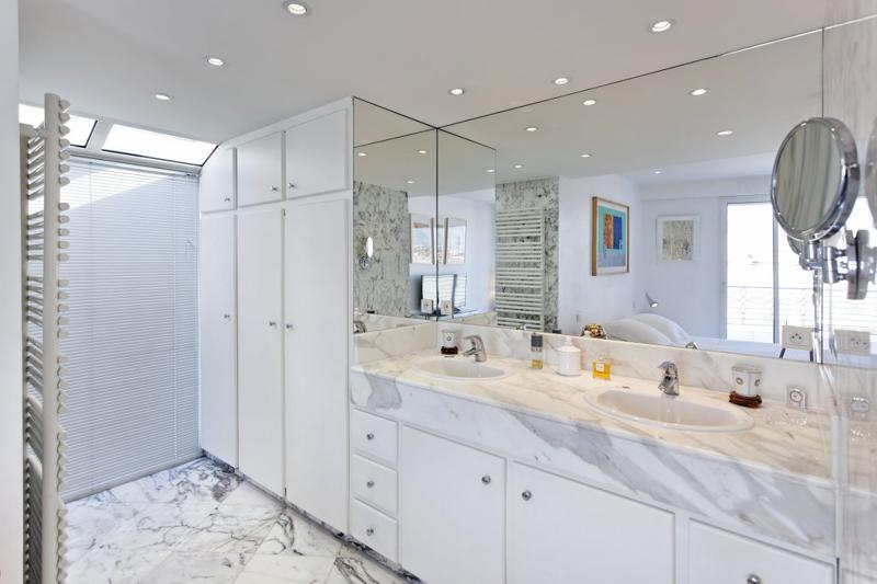 A large mirror in the modern bathroom with white cabinets and walk-in closet in a Cannes penthouse
