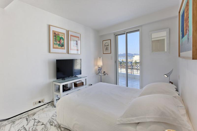 Double bedroom with white sheets and pillows, a tv and a terrace in a Cannes 1 bedroom penthouse with sea views