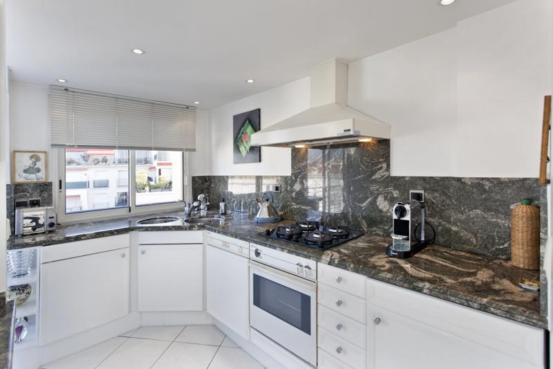 Kitchen with white drawers and cabinets and equipped with oven, microwave, coffee maker, kettle and stove in Cannes