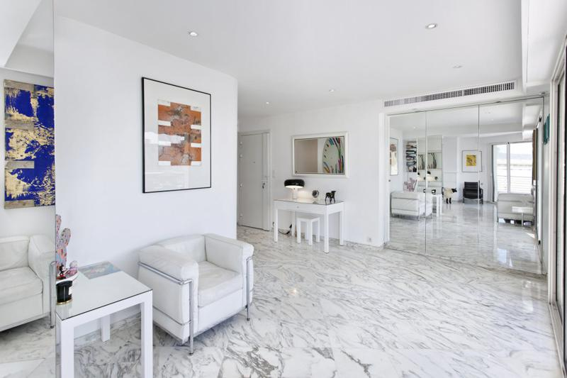 White sofa and a full length mirror in the lobby of a Cannes penthouse with marble flooring