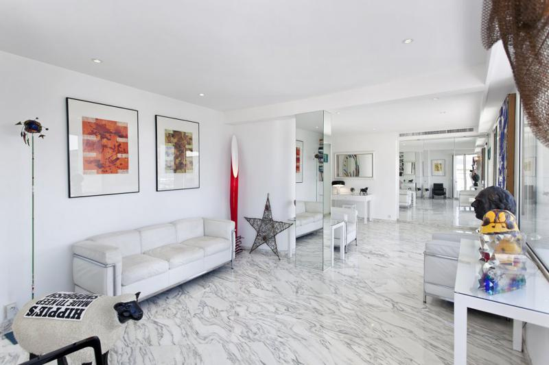 White themed living room with couches and paintings on the walls in a Cannes 1 bedroom penthouse for rent.