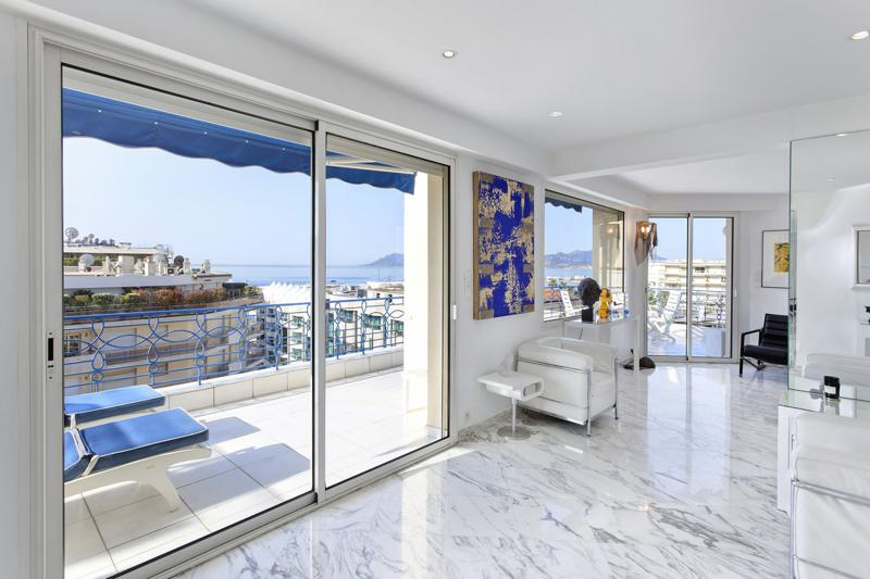 Living room with couches and sofa and glass doors opening to the terrace with panoramic views in a Cannes rental penthouse