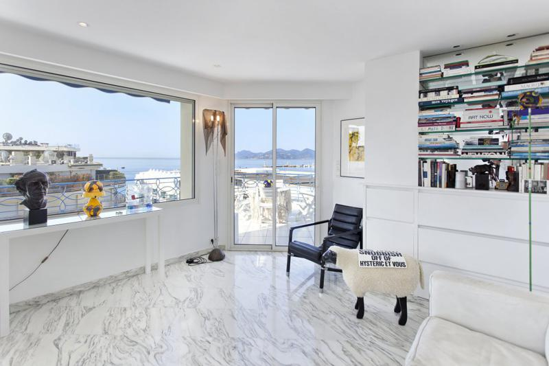 Bookshelf, couch and chair for meetings the room with white walls and marble floor for meetings in a Cannes event penthouse.