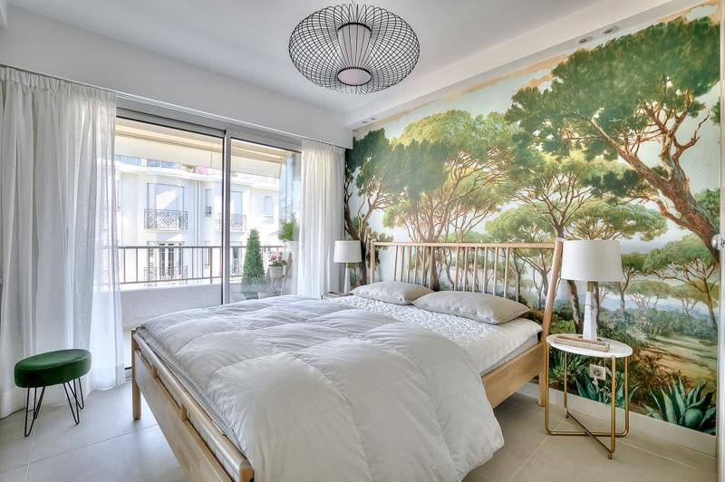 Double bed with wooden frame and a green stool in the corner of a bedroom with access to terrace in a Cannes rental apartment