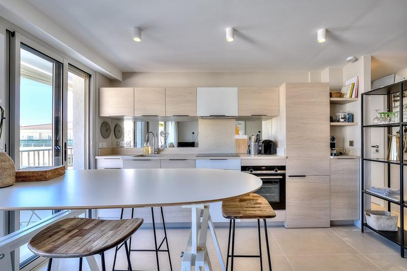 Dining table with stools in the open kitchen in a Cannes apartment close to the convention centre