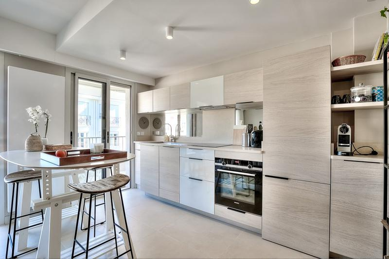 Breakfast bar with stools in the open kitchen with oven, coffee maker, induction stove and access to the terrace in Cannes