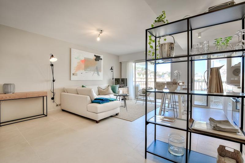 Modern living room with beige coloured interiors, a sectional sofa and an open kitchen in Cannes 1 bedroom accommodation
