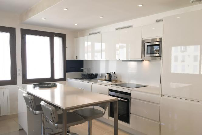 Open plan fully equipped kitchen with metallic countertops and dining table with chairs in a Cannes