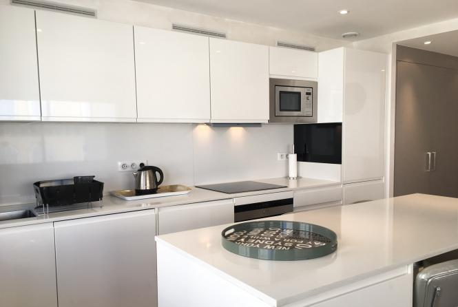 White metallic countertops in the kitchen with microwave, kettle, oven and induction stove.
