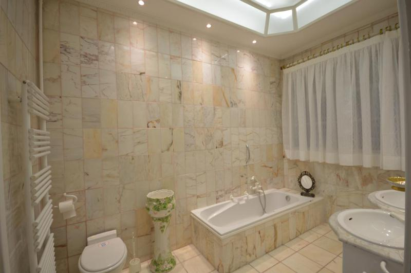 Bathroom with cream tiles, a bathtub and a double vessel sink in Cannes