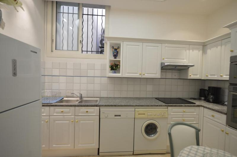 White kitchen with a refrigerator, dish washer, washing machine, a table and a chair
