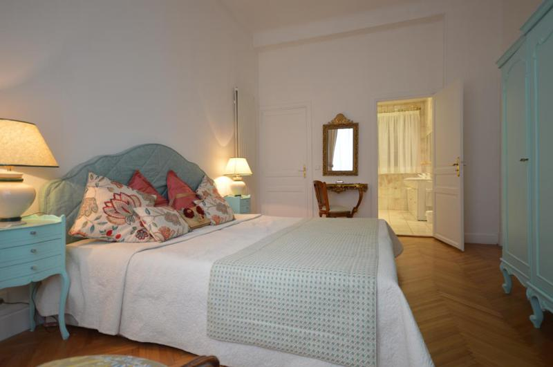 Wooden floored bedroom with attached bathroom, light green coloured closet and side tables in a Cannes rental apartment