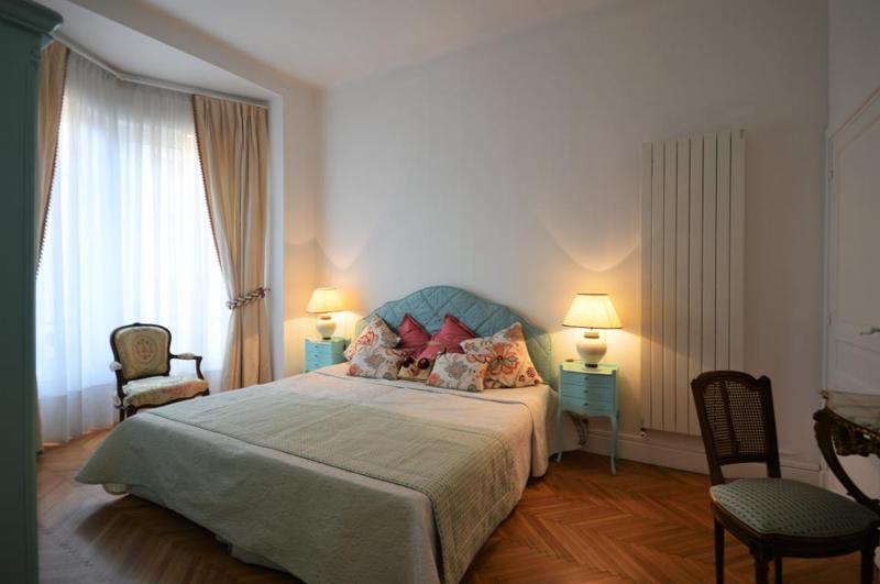Double bedroom with chairs, dressing table, large window and a wall heater in a Cannes rental accommodation
