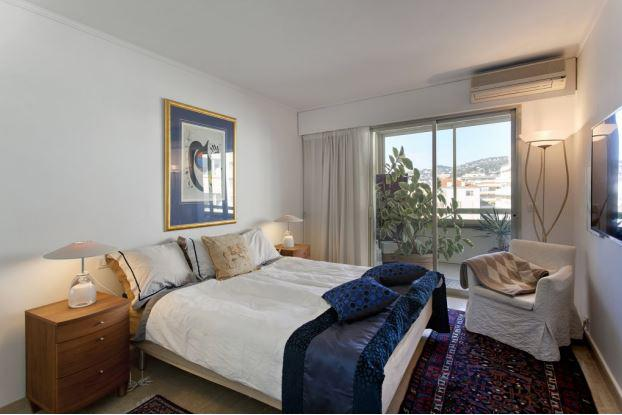 Double bedroom with a sofa chair and an air conditioner in a bedroom with a terrace in Cannes