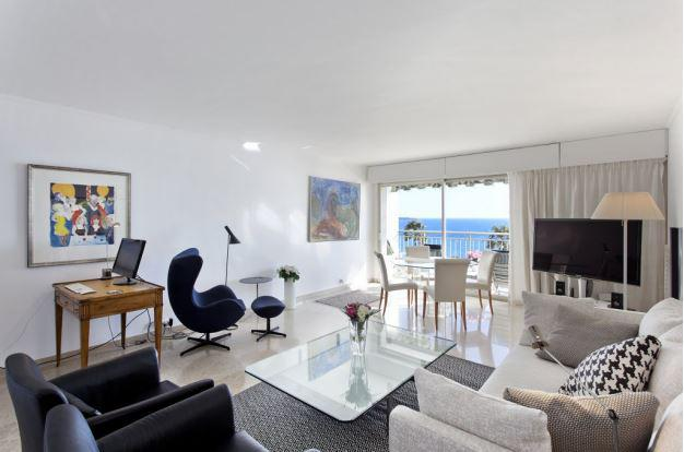 A wooden office desk with a pc for meetings in the furnished living room with sea views in a 2 bedroom Cannes group apartment