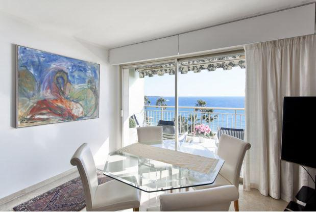 Glass table with cream leather chairs, a tv and a terrace with lounge chairs in a Cannes seafront group accommodation