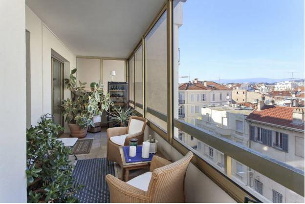Indoor terrace with plants, chairs, table and view of Cannes city in a 2 bedroom group rental accommodation