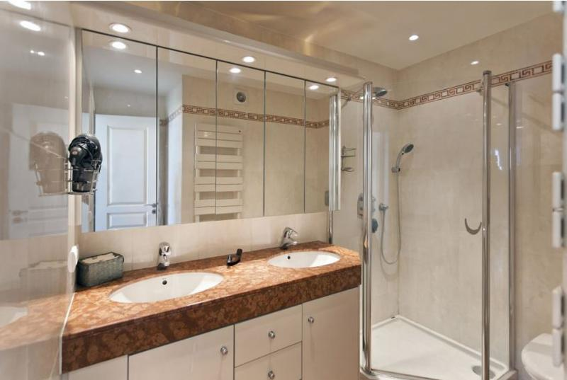 Bathroom with standing shower and dual sink with mirror cabinets over it