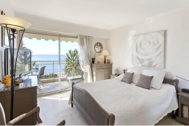 Brown bed frame with white mattress and covers in a double bedroom with a sea view terrace for Cannes corporate rental